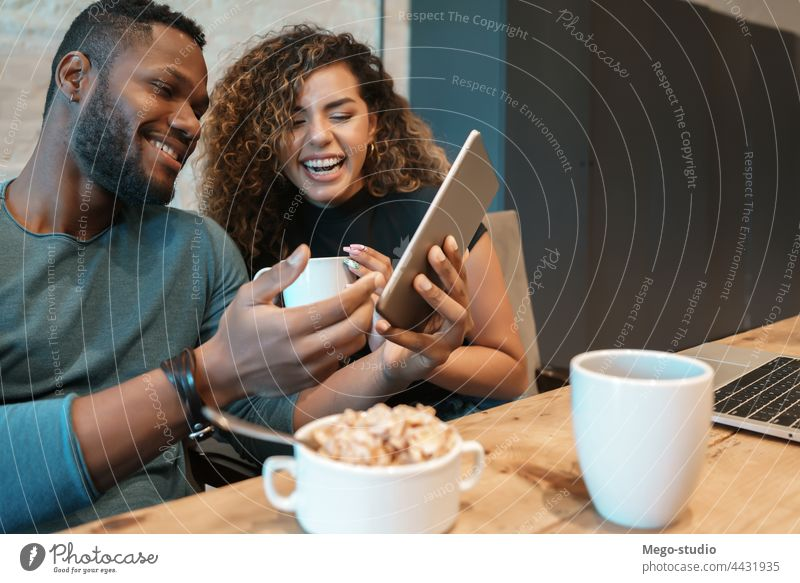 Couple using a digital tablet while having breakfast. young couple together indoors lifestyle quarantine food kitchen technology enjoying sitting woman home two