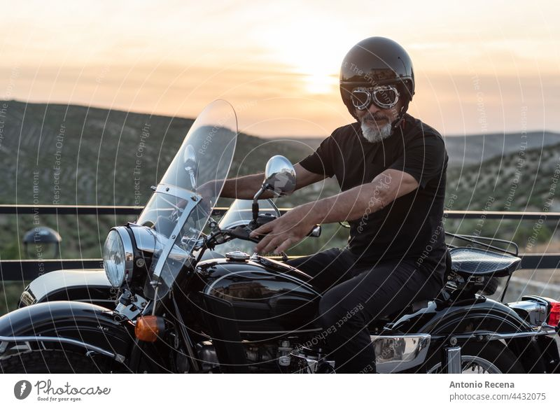 Mature bikeron sidecar bike mature men adult person 60-65 years middle eastern people lifestyles side view profile goatee helmet loking at camera attractive