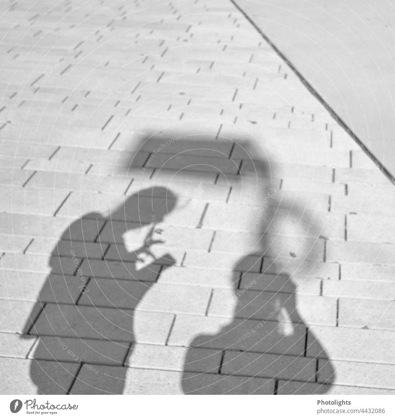 Shadow play 2 persons Contrast Human being smartphone at the same time Street Town pavement Ground Exterior shot people Silhouette in common To go for a walk