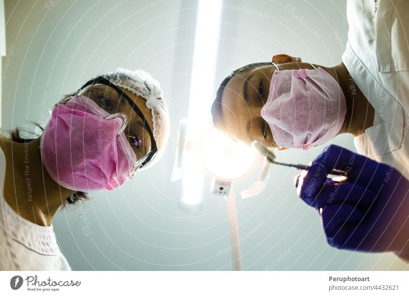 Portrait of two surgeons at work, operating in uniform, looking at the camera. covid-19 coronavirus nurses hospital doctor people group health operation