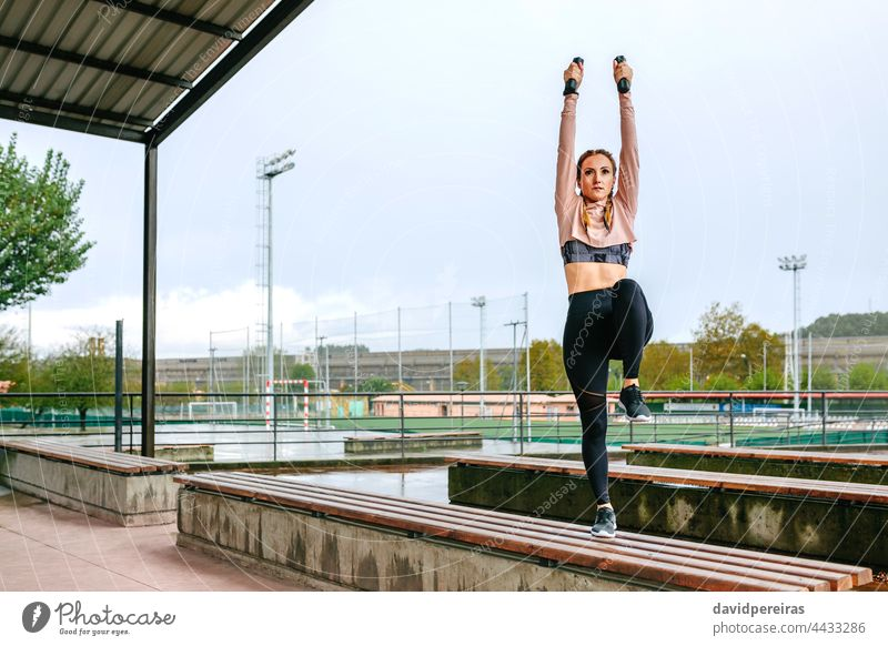 Young woman training with dumbbells outdoors arms up stretching leg knee copy space power exercise warm up young on a bench healthy female fitness girl sport
