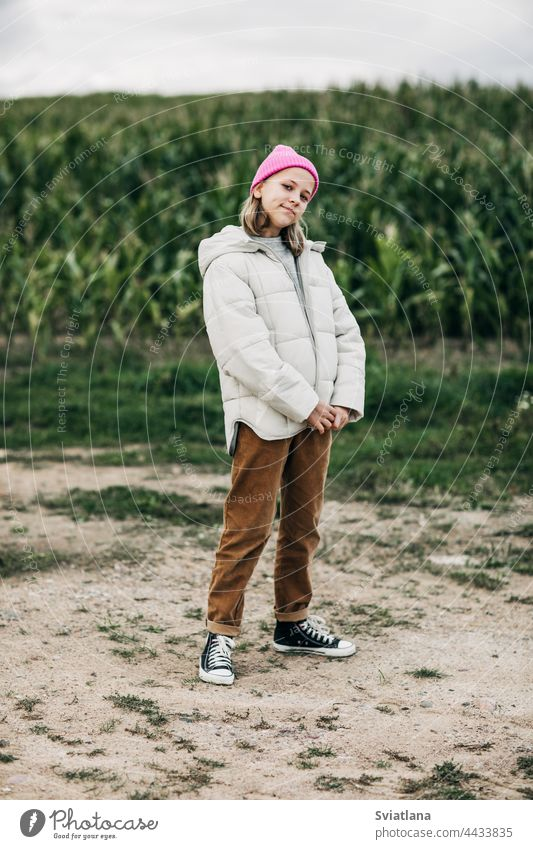 A teenage girl in a stylish image and a pink cap stands against the background of a corn field autumn yellow cornfield teenager cloak laugh lifestyle play cute