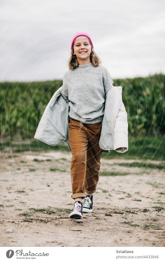 Cheerful beautiful teenage girl in yellow raincoat and pink hat confidently walks in the corn field autumn cornfield teenager cloak laugh lifestyle play cute