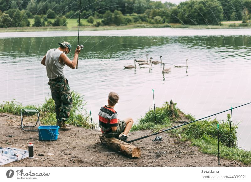 A young man teaches his children to fish during a family vacation at a camping site. Hobbies, vacations, weekends, fishing together boy lake shore teaching dad