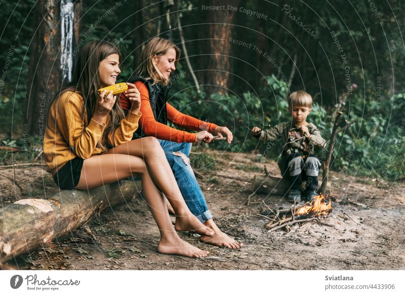 A young mother with her children is sitting by the campfire during a joint holiday, a girl is eating corn camping mom kids weekend hike daughter son together