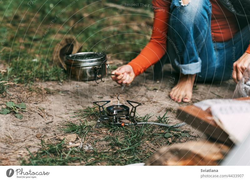 A woman cooks food with a portable gas burner in the forest female activity tourism camp outdoor nature adventure travel picnic hiking girl tourist trip