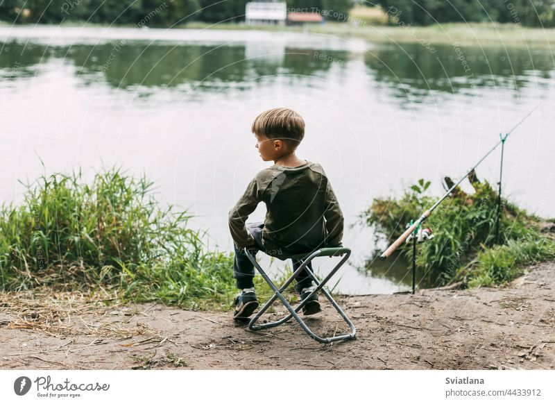 The boy is sitting on a folding chair on the shore of a lake or river. Recreation, weekends, tourism. Rear view child summer kid recreation lifestyle leisure