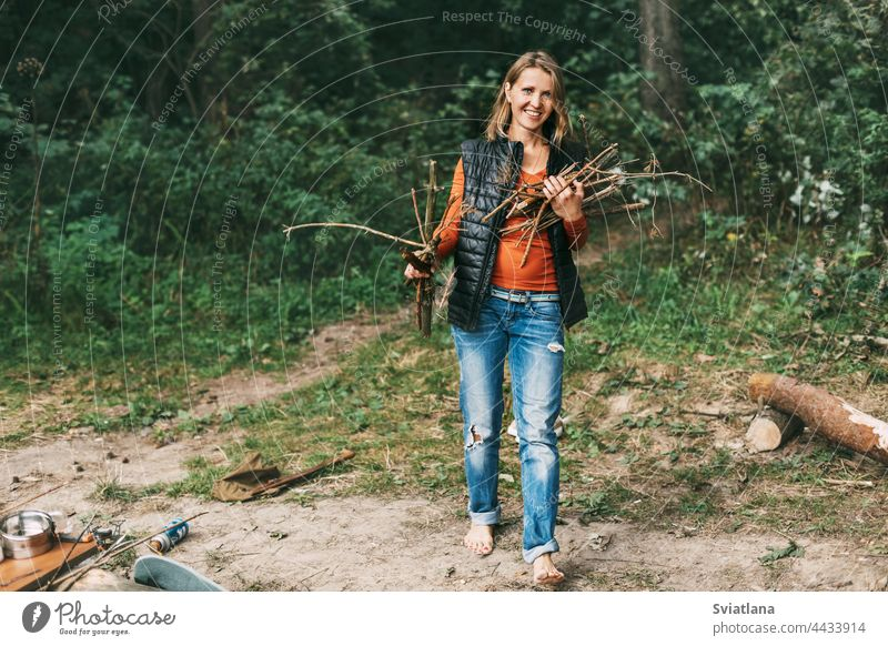 A tourist girl in nature collects firewood for a fire. A woman in close-up. The concept of travel and adventure camping bonfire brushwood outdoors forest female