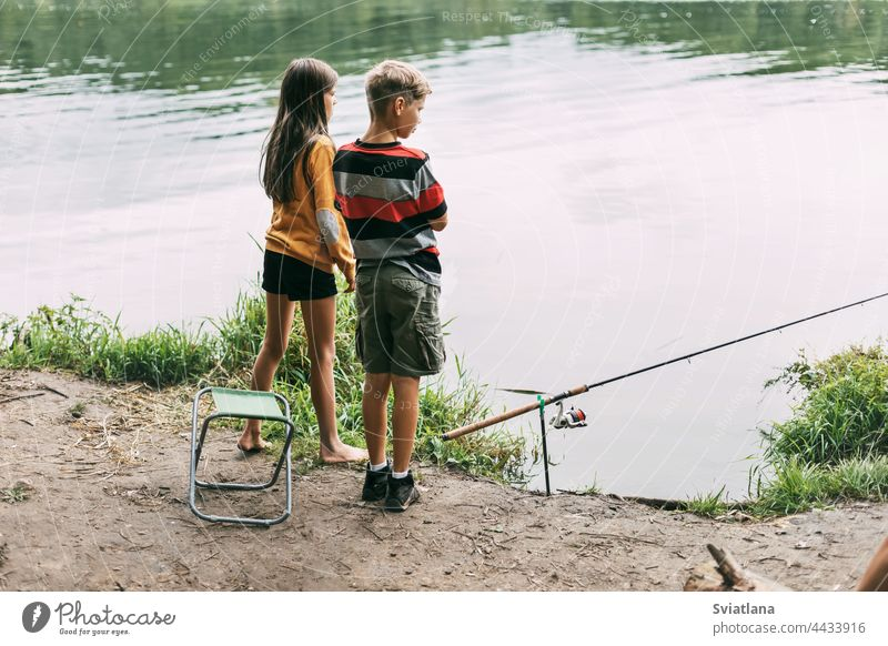 A brother and sister are standing on the river bank and fishing during a family vacation at a camping site. Time together, family vacation boy girl child