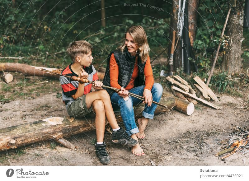 A mother and her teenage son are sitting on a tree in campsites and trying grilled sausages cooked on a fire camping family mom man spending time together