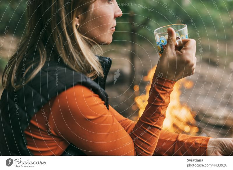 Close-up of an adult woman sitting with a cup of tea by the fire while relaxing in the forest camping drink young nature tourist adventure vacation campfire