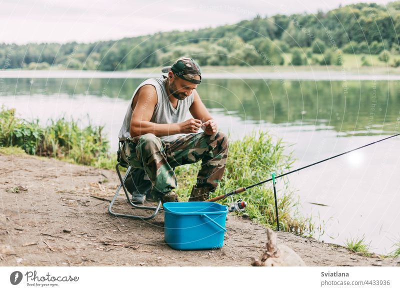 A young fisherman catches fish on a lake or river, prepares tackle and bait. Hobbies, weekends, fishing water adult one sitting chair hunting equipment hand rod