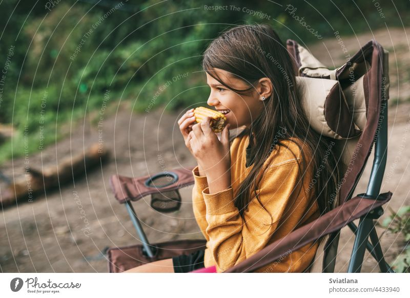 A teenage girl in a bright yellow sweater is sitting in a camping chair on the shore of the lake and eating corn woman nature female people vacation relaxation