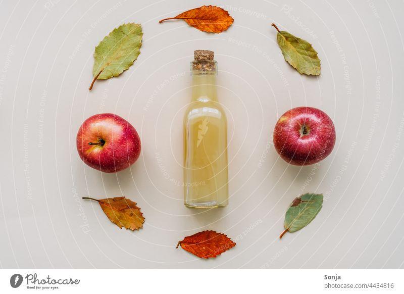 Natural cloudy apple juice in a glass bottle and autumn leaves Apel juice Apple Glassbottle Fresh framed Design plan Beverage Juice Healthy Eating Diet