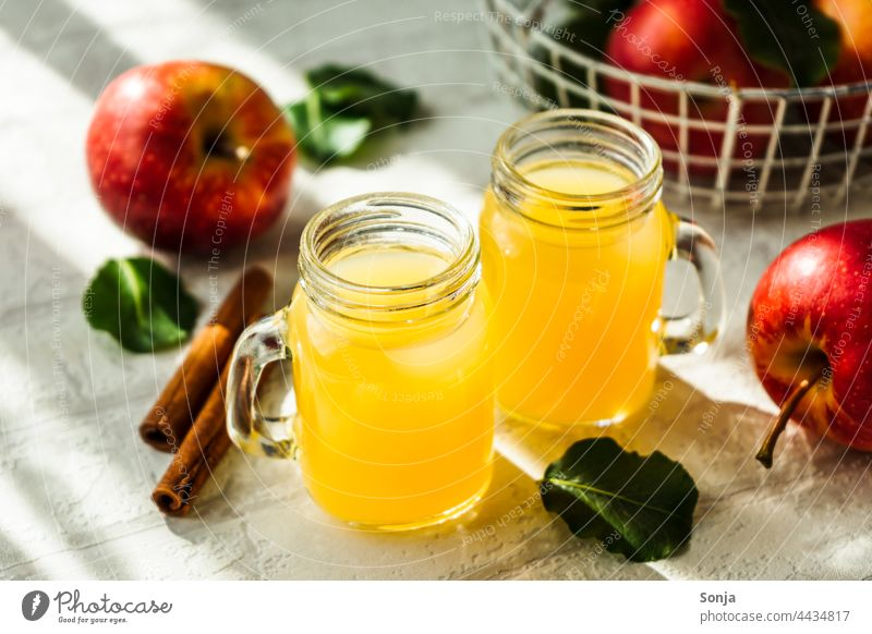 Fresh apple juice in two glasses and red apples on a white table Apple Juice Glass Red Beverage Cold drink Breakfast Delicious Drinking Interior shot Lemonade