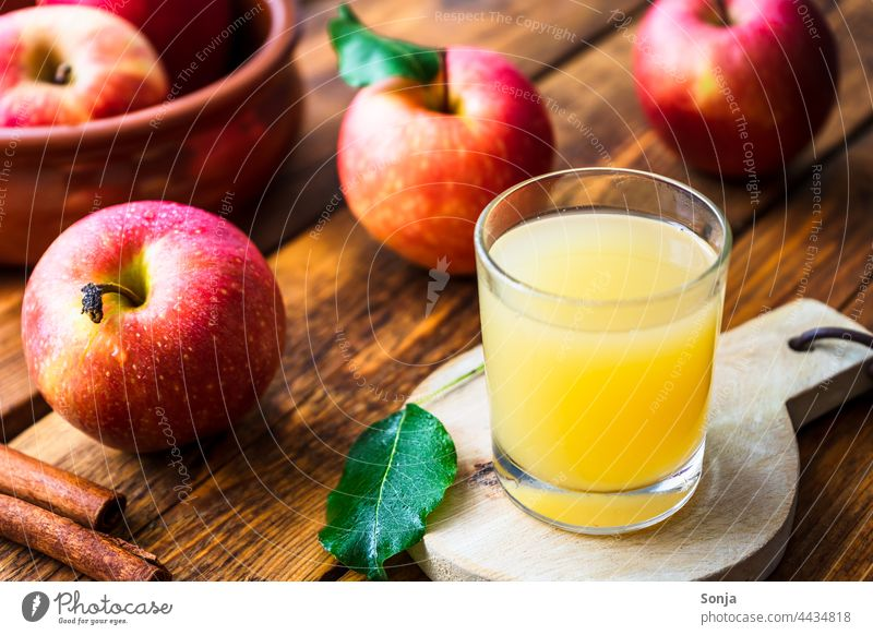 Fresh apple juice in a glass and red apples on a wooden table Apple juice drinking glass Wooden table Autumn Delicious Organic produce Interior shot