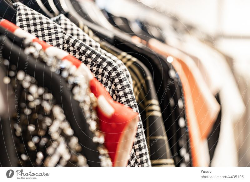Fashionable stylish women's clothing on a hanger. Close-up of branded clothing in a show room. Light background. Fashion retail, show room, shopping or seasonal sale concept. Selective focus