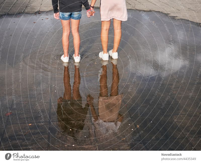 Rear view of two girls holding hands and standing on a water puddle, no faces are shown teenagers young female together friends friendship beautiful youth