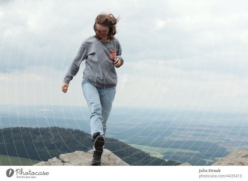 high up Woman Walking in process hair in the wind Hair on the face Wind windy Mountain Mountaineering Rock Rhön Landscape Sky Clouds Clouds in the sky forests