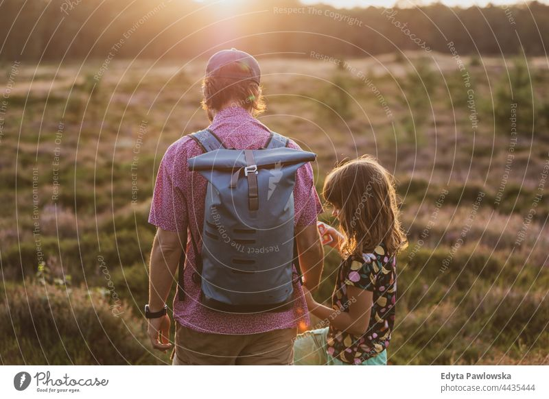 Father and daughter on a hike in the forest during sunset together father parent love back backpack walk meadow grass field rural countryside adventure
