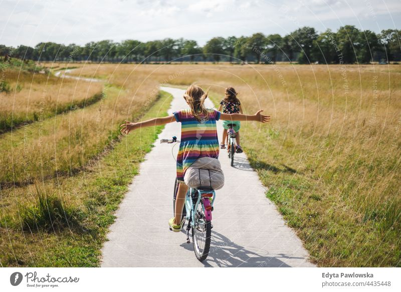 Little girl riding a bicycle with her arms outstretched safe safety Netherlands bike cycling riding bike cycle routes vacation travel active adventure