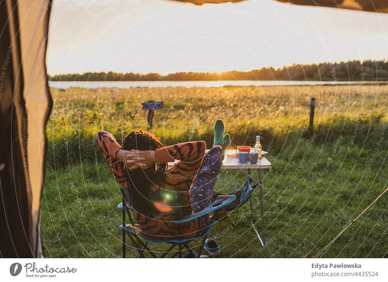 Woman relaxing in front of the tent during sunset campsite camping meadow grass field rural green countryside adventure hiking Wilderness wild vacation travel