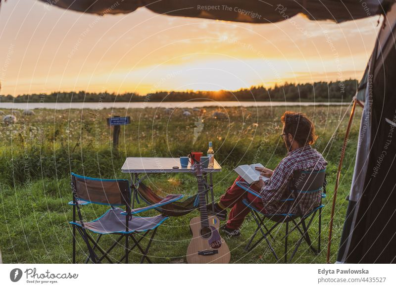 Man reading a book at a campsite. View from a tent camping meadow grass field rural green countryside adventure hiking Wilderness wild vacation travel active