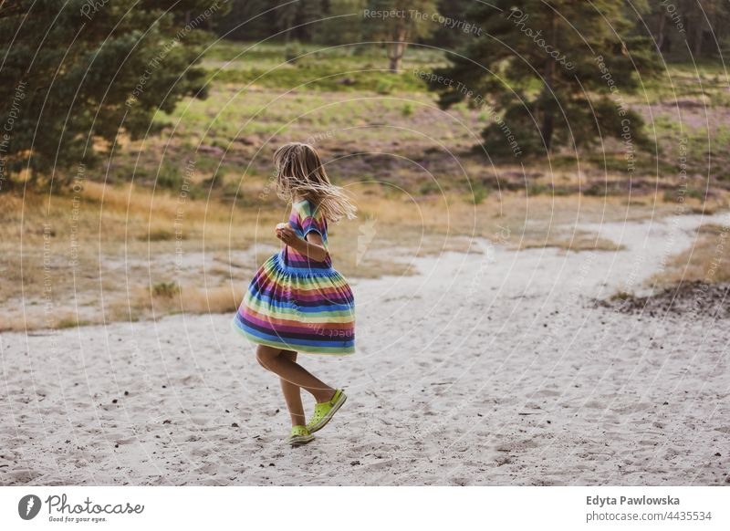 Little girl dancing in nature meadow grass field rural countryside adventure Wilderness wild hair vacation travel active summertime day freedom holiday enjoying