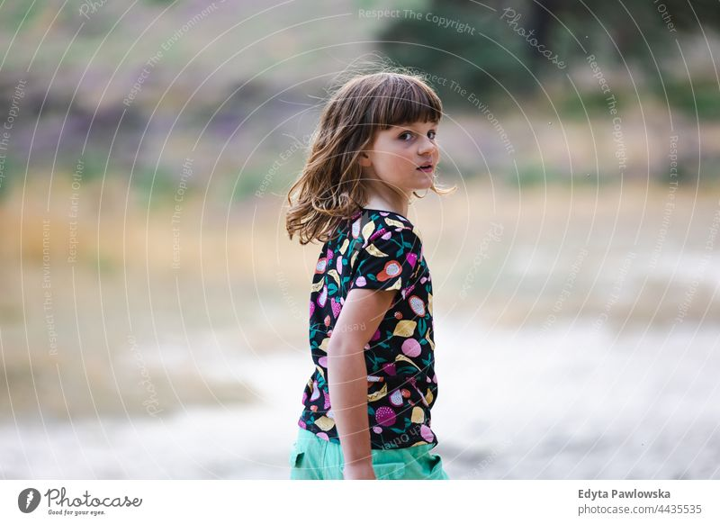 Little girl on a meadow full of heather at sunset grass field rural countryside adventure Wilderness wild hair vacation travel active summertime day freedom