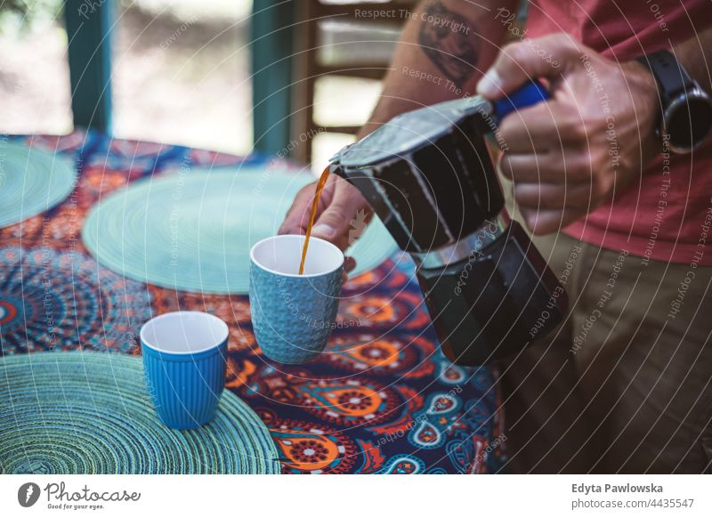 Man pouring coffee from a coffee maker into a cup coffee cup hands drink food fresh freshness barista making home house domestic hipster cafe beverage mug hot