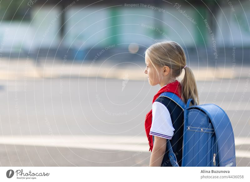 Back to school. Little girl from elementary school outdoor on bus stop. Kid going learn new things 1th september back to school child public transport backpack