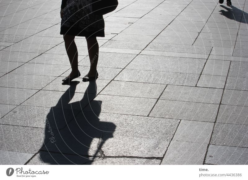 on the way Silhouette Shadow urban Woman sunny Concrete slabs Floor covering Places In transit crossing Back-light