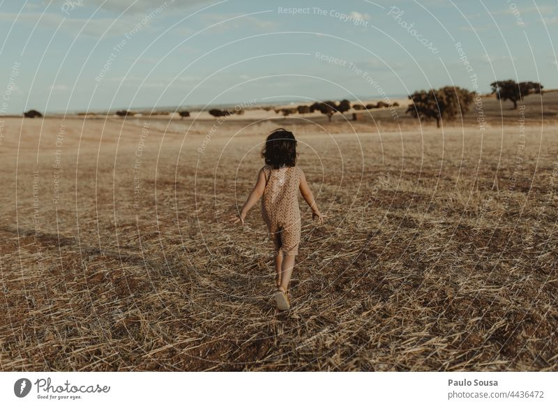 Rear view girl running through fields Child 1 - 3 years Girl Running Freedom Nature Authentic Joy Playing 3 - 8 years Infancy Exterior shot Colour photo