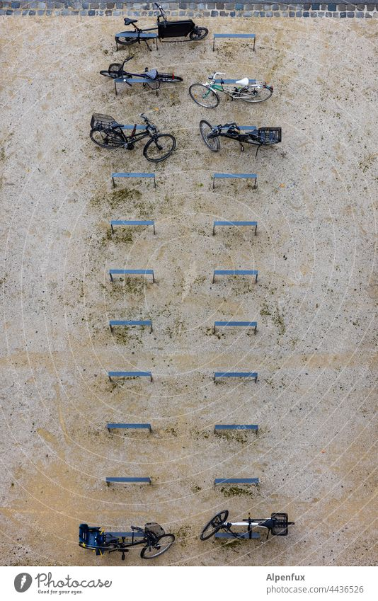 Partially | occupied bicycle parking Wheel bicycle stand Bicycle Exterior shot Parking lot Cycling Bicycle rack Town Means of transport Deserted Transport