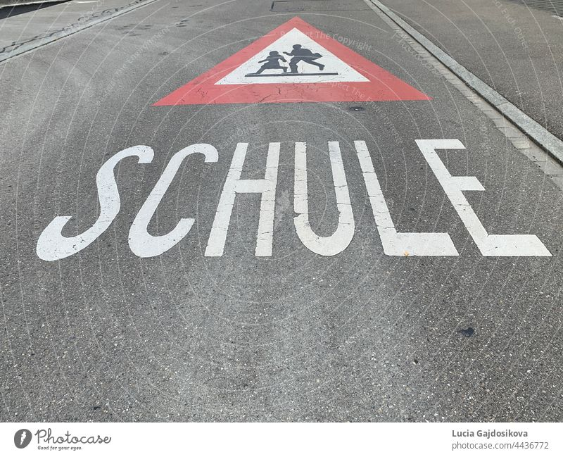 Warning sign of the way to school in German language  in Switzerland. Road sign is red triangle with running children in white field and text Schule, which means School.