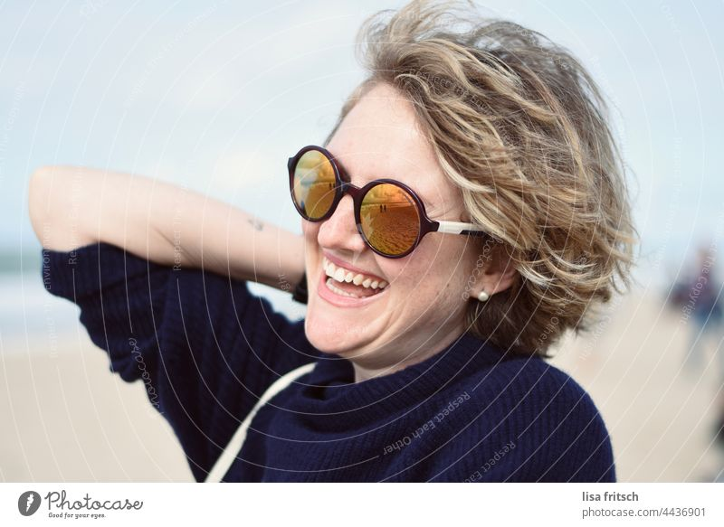 WOMAN - SUNGLASSES - AT THE SEA Woman 30-34 years Sunglasses Curl Blonde Laughter by the sea Adults Exterior shot Colour photo Joie de vivre (Vitality)