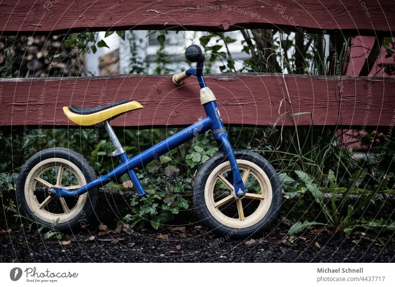 Old wheel on the fence impeller Child Infancy Exterior shot Movement Toddler Bicycle Playing Former Past Review Longing melancholically melancholy Meditative