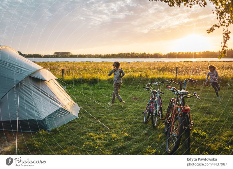 Children playing on the campsite running playful fun joy children family kids camping tent bike cycling meadow grass field rural green countryside adventure