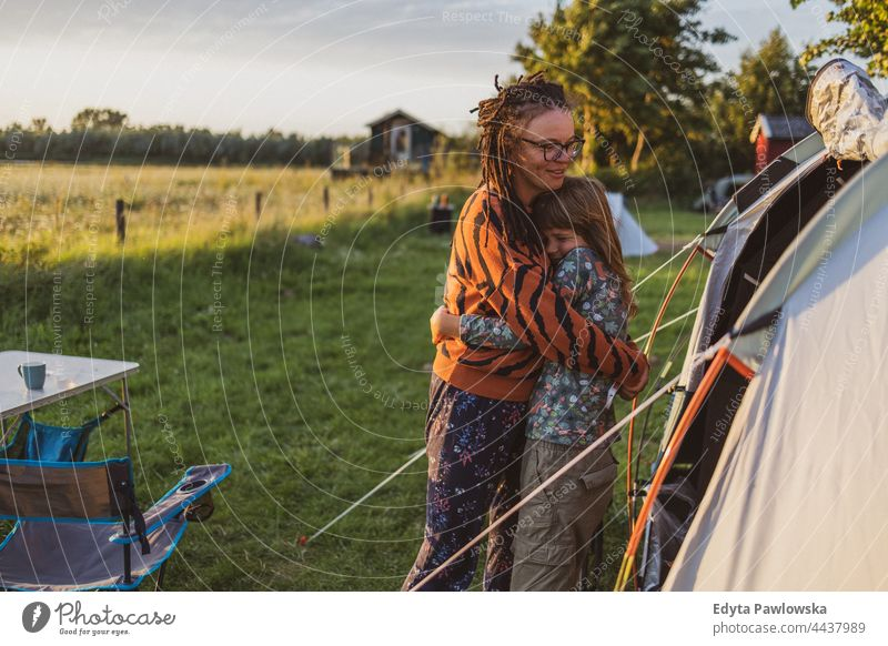 Mother and daughter hugging in front of the tent at the campsite mother parent together love fun joy children family kids camping bike cycling meadow grass