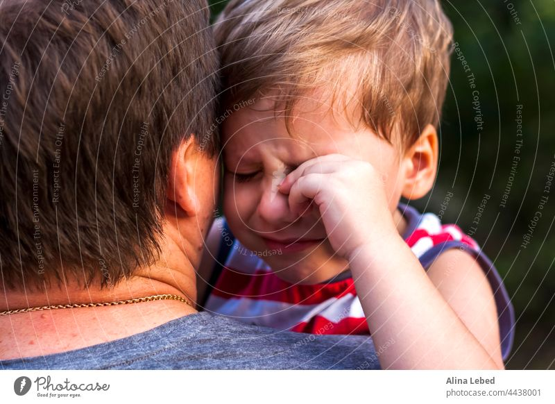 A little boy is crying while being in his father's arms, snuggling up to him to feel protected. expression caring relationship child son white parent sitting