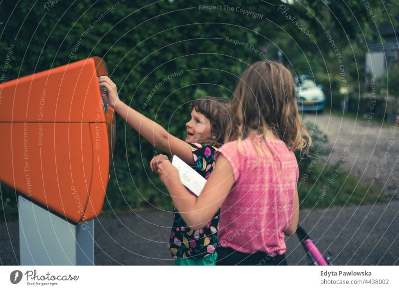 Children putting a postcard in the mailbox, Netherlands posting letter postbox sending letter friendship together vacation adventure summertime day enjoying