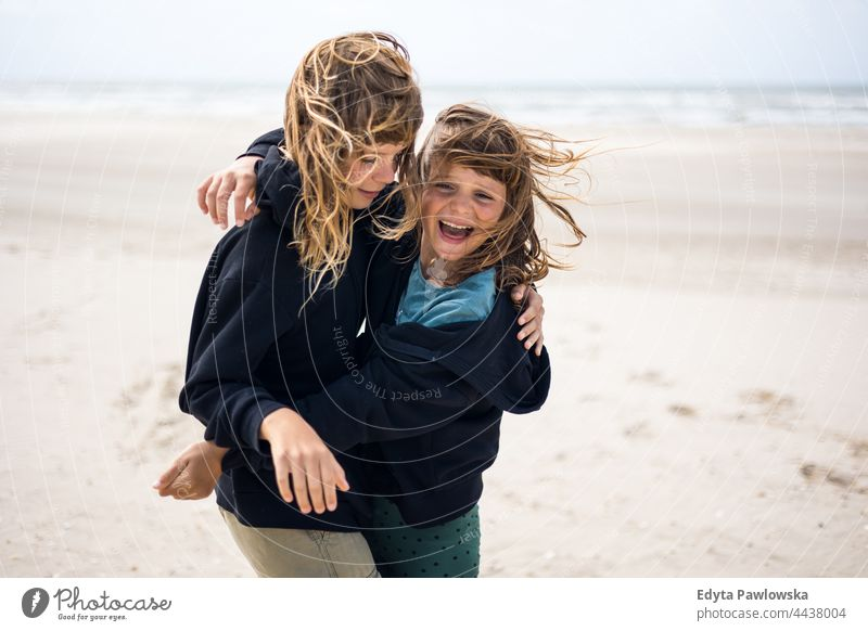 Two sisters playing on the beach friendship sisterhood love together sea sand sky water vacation travel active adventure summertime day freedom holiday enjoying