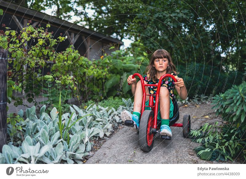 Little girl riding a bike in the park cycling riding bike garden vacation active adventure summertime day freedom holiday enjoying outside serious outdoors