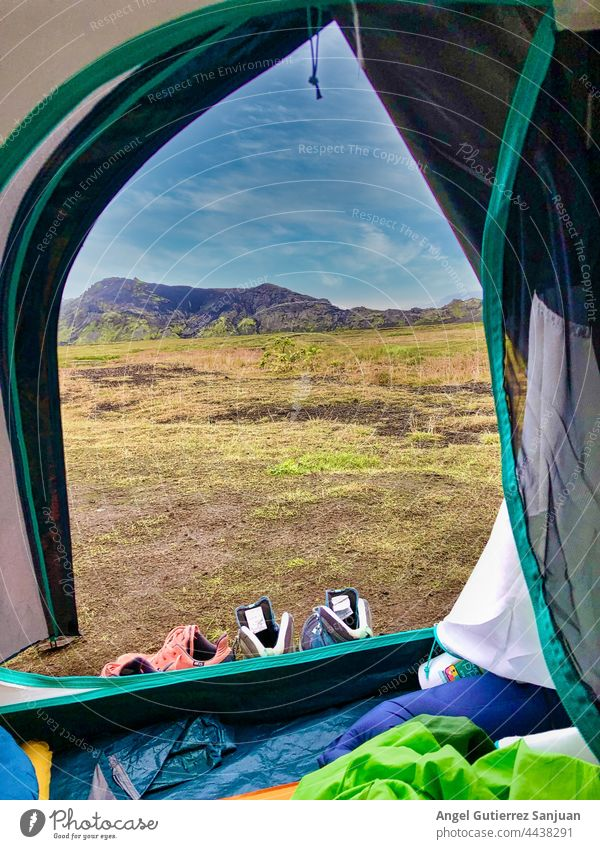 Tent placed on meadow in mountains tent camp campsite highland rock range field landscape nature scenery scenic wild environment majestic grass lawn rocky