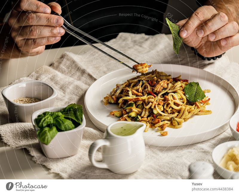 Traditional pasta with seafood. The chef prepares a pasta marinara. The chef decorates the dish with tweezers. Spaghetti with seafood. Mediterranean Kitchen. People at work. Close-up. Body parts