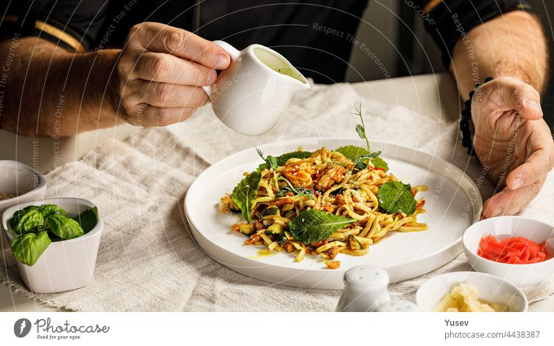 Spaghetti with seafood. The hands of the head chef prepares a traditional pasta with seafood. The cook pours the sauce over the dish. Restaurant serving dish. Mediterranean Kitchen Banner