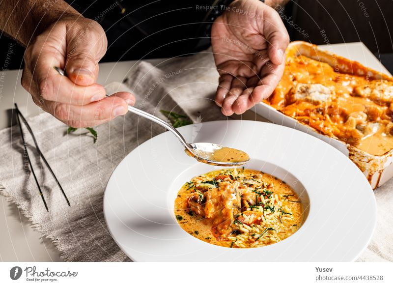 Authentic Spanish paella with cod and mussels. Traditional Mediterranean seafood dish. The chef prepares the dish. Restaurant dish serving. Close-up. People at work. Body parts