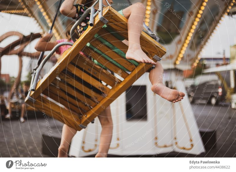 Children having fun on carousel ride feet foot bare feet merry-go-round riding swings fairground funny together amusement park vacation adventure summertime day