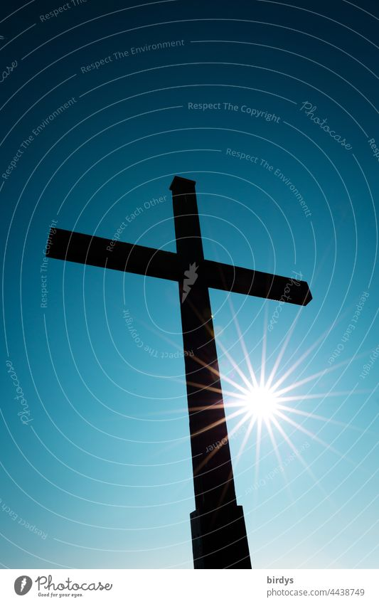 Christian cross with shining sun in front of cloudless blue sky Crucifix Sunbeam Cloudless sky Christianity Religion and faith Symbols and metaphors Church Hope