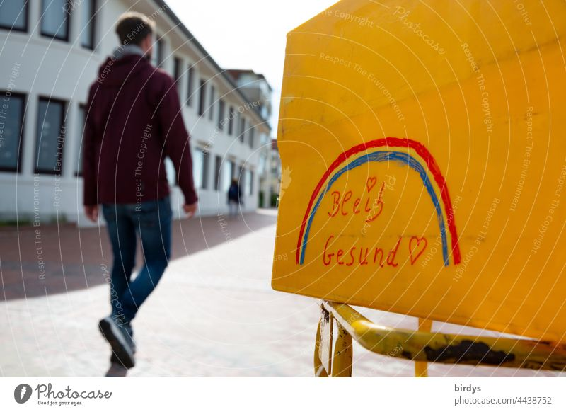 Stay healthy ! Inscription with rainbow on a yellow box. In the background a young man walks by. Corona, Pandemic, Vaccinate corona covid19 inoculate sb.